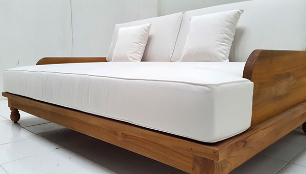 grade A teak garden daybed with natural finish with weatherproof white garden mattress and throwing pillows