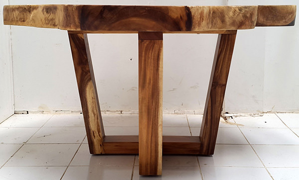 round suar coffee table with natural shape and crossed legs