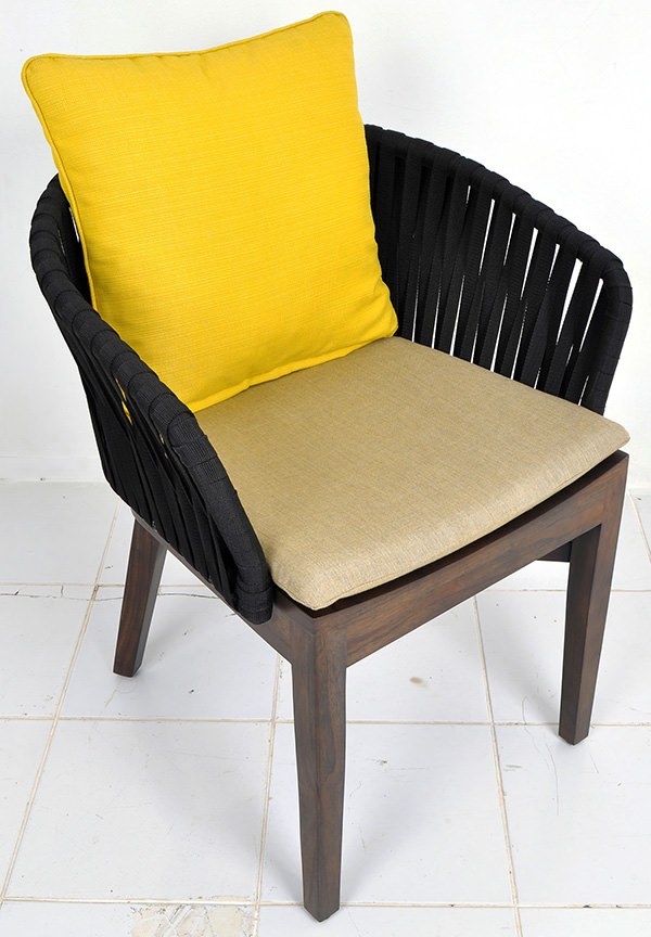 curved outdoor chair with teak seat and black ropes backseat and linen seat cushion