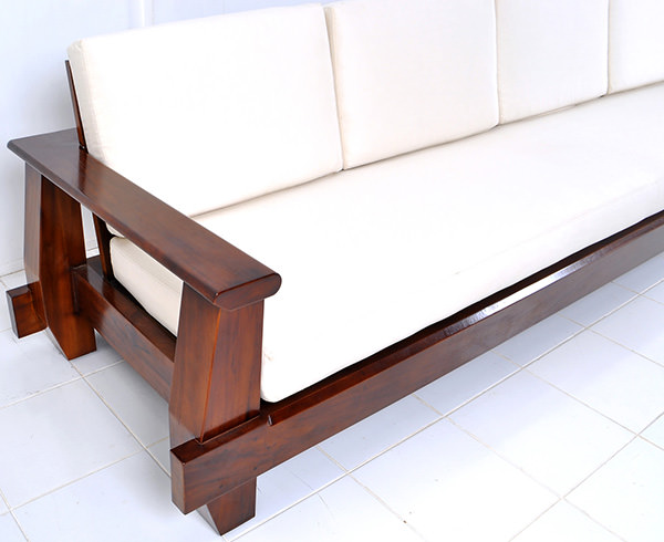 indoor dark brown wooden couch with white cushions