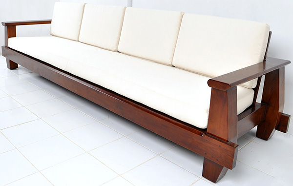dark brown wooden couch with white cushions