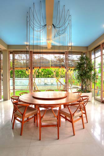 The natural teak round table seamlessly blend with the tropical surroundings of the house